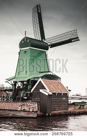 Windmill Under Cloudy Sky On Zaan River Coast, Zaanse Schans Town, Popular Tourist Attractions Of Th