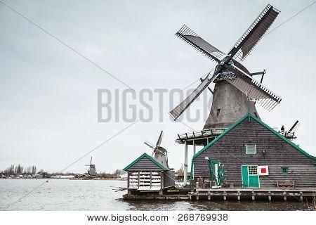 Old Wooden Windmills On Zaan River Coast, Zaanse Schans Town, Popular Tourist Attractions Of Netherl