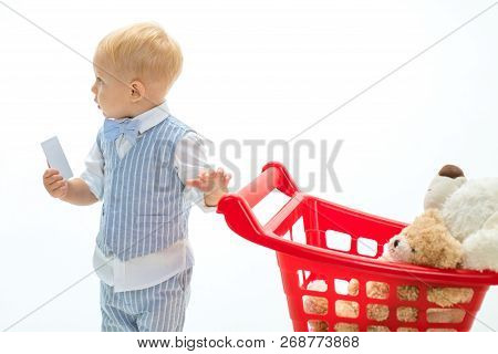 Little Boy Child In Toy Shop With Credit Card. Savings On Purchases. Little Boy Go Shopping With Ful