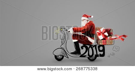 Santa Claus on scooter delivering Christmas or New Year 2019 gifts at gray background