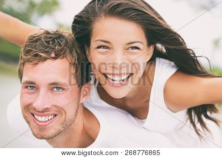 Happy couple having fun piggybacking laughing on summer honeymoon holidays vacation on beach. Beautiful interracial multi-ethnic dating people on wedding, Caucasian man and Asian woman.