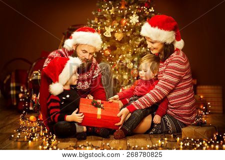 Christmas Family Opening Present, Xmas Tree And Gifts, Happy Father Mother Child And Baby In Sweater