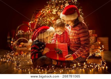 Christmas Family Opening Lighting Present Gift Box Under Xmas Tree, Happy Mother And Children In Mag