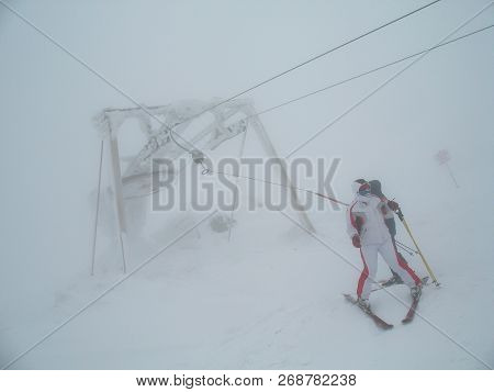 Icy Ski Lift With Inexperienced Skier In In Thick Fog. Skiers In The Fog On A Snowy Mountain. In The