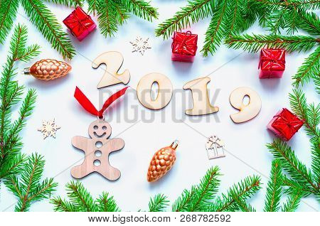 New Year 2019 background with 2019 figures, Christmas toys, blue fir tree branches. Flat lay, top view of New Year 2019 festive composition, 2019 still life