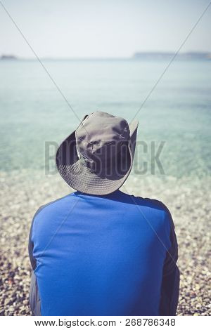 Tourist wearing a hat standing on a beach and looking at the stunning Croatian coast in Dubrovnik poster