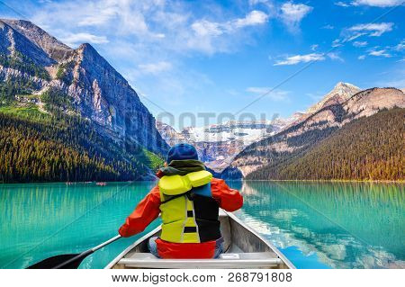 Teen Boy Canoeing On Lake Louise In Banff National Park Of The Canadian Rockies With Its Glacier-fed