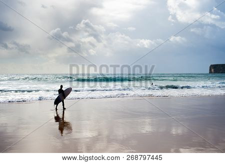 Surfer With Surfboard Walking On The Beach At Sunset. Algarve, Portugal