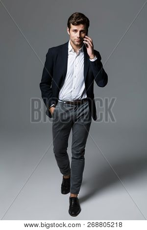 Full length portrait of a confident young businessman dressed in suit isolated over gray background, walking, talking on mobile phone