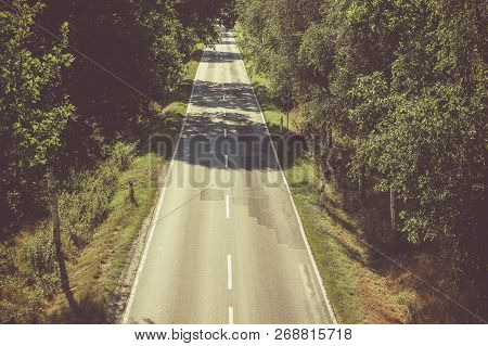 A Straight Road Disappearing Into The Trees. A Straight Road Travelling Through A A Forest, Maybe Si
