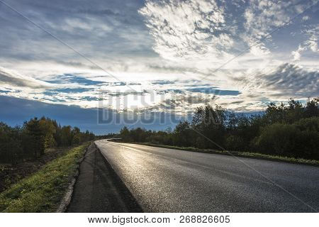 Asphalt Road In Bright Back Sunlight In The Early Cloudy Morning, Russia.