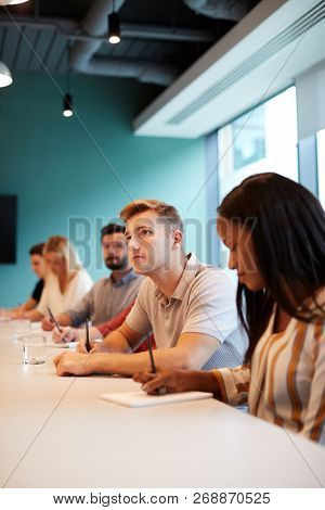 Group Of Young Candidates Sitting At Boardroom Table Making Notes At Presentation At Business Graduate Recruitment Assessment Day