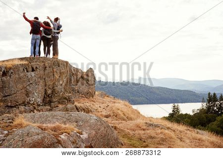 A group of five young adult friends embrace with arms in the air after arriving at summit during mountain hike, back view