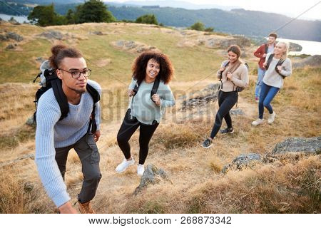 A multi ethnic group  of five young adult friends smile while climbing to the summit during a mountain hike, close up