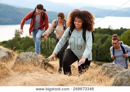 A multi ethnic group of young adult young adult friends smiling while climbing to a mountain summit, close up