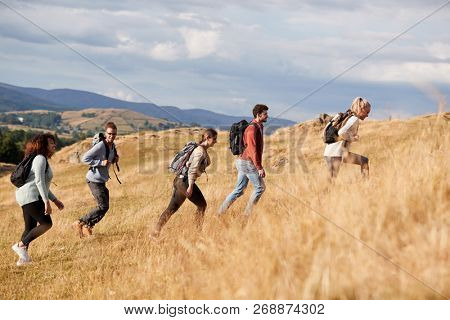 Multi ethnic group of happy young adult friends climbing a hill during a mountain hike, side view poster
