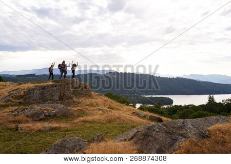 A group of five happy young adult friends cheer with their arms in the air at the summit after a mountain hike