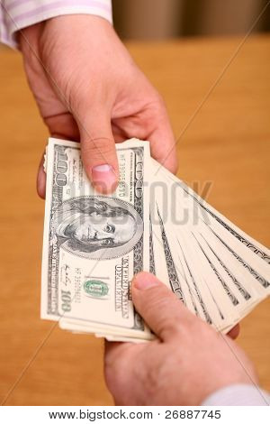 Two businessmen giving and taking dollars over wooden background