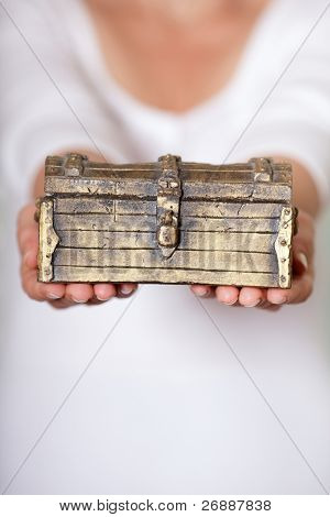 Woman holding a locked antique chest in her hands