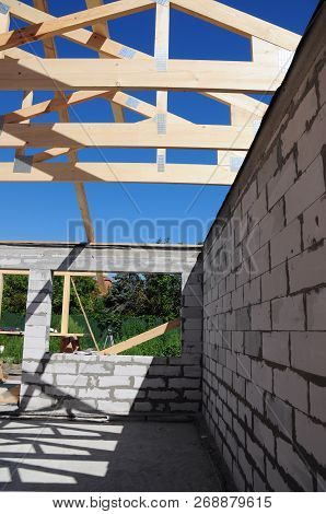 House Construction With Roof Beams, Trusses, Wooden Frame Beams On Rooftop.