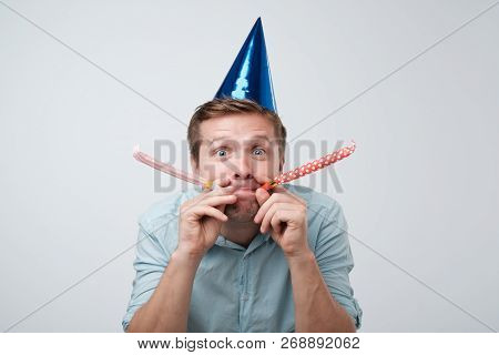 Cheerful Young Man Having Fun On Party Wearing Blue Denim Shirt And Holiday Hat, Blowing Party Horn.