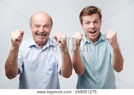 Photo Of Joyful Two Young Men Clench Fists And Shout With Happiness, Dressed Casually