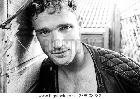 Portrait Of Handsome Blonde Man With Open Leather Jacket And Stubble Looking At Camera