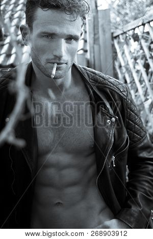 Handsome Blonde Man With Open Leather Jacket Revealing Sixpack Abs Smoking Cigarette And Looking At