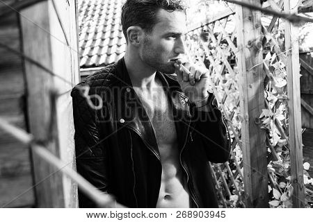 Handsome Blonde Man With Open Leather Jacket Revealing Sixpack Abs Smoking Cigarette And Looking Awa