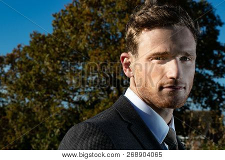 Good Looking Man Dressed In A Suit In Countryside With Trees And And Blue Sky In Background