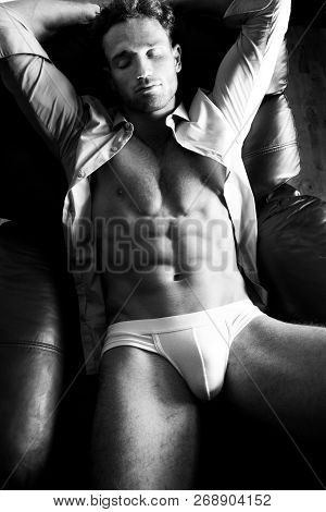 Semi Naked Handsome Blonde Man Sleeping In Leather Armchair With Open Shirt Revealing Sixpack Abs An