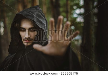 The Black Monk Pointing His Finger In The Woods