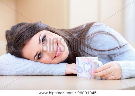 Young happy Woman in warme Pullover trinken eine Tasse heißen Tee