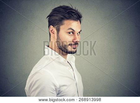 Young Dishonest Man In White Shirt Looking With Pretend Smile At Camera On Gray Background