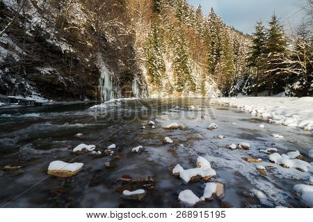 Lovely Winter Scenery By The River. Snow Covered Banks And Trees. Frozen Waterfall In The Distance.