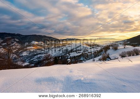 Winter Sunrise In Mountainous Rural Area. Leafless Trees On Snow Covered Hills Under The Beautiful B