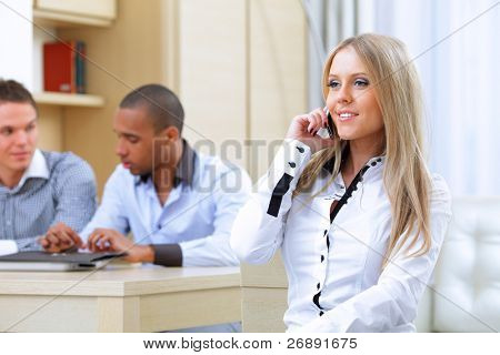 Portrait of young happy caucasin woman on phone with her business partners on the background