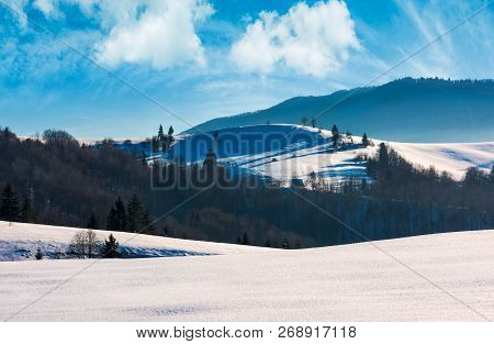 Mountainous Landscape On A Bright Winter Day. Wonderful Cloudscape Above The Snow Covered Hills Roll