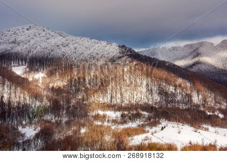 Lovely Winter Landscape In Mountains With Snowy Tops In Dappled Light And Cloudy Sky Above The Ridge