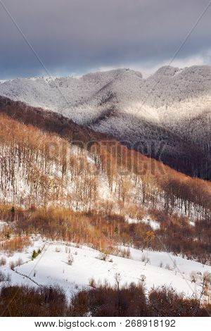 Lovely Winter Scenery In Mountains With Snowy Tops In Dappled Light And Cloudy Sky Above The Ridge.