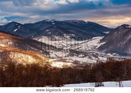 Beautiful Winter Scenery Of Carpathians. Village Down In The Valley In Dappled Light. Gorgeous Eveni