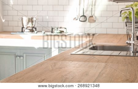 Kitchen Room And Background Concept - Blurred Brown Wooden Top Of Kitchen Counter With Beautiful Mod