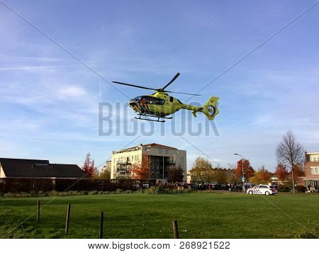 Tiel, The Netherlands - November 14, 2018: Yellow Medical Helicopter Taking Off After Assisting In M
