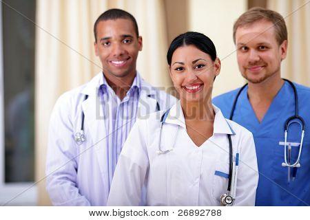 Multi-ethnic team of confident happy doctors