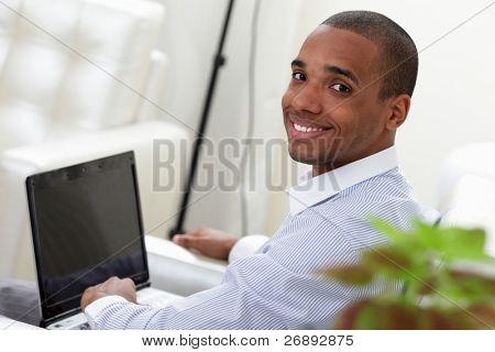 Retrato de um homem de negócios jovens trabalhando em um laptop