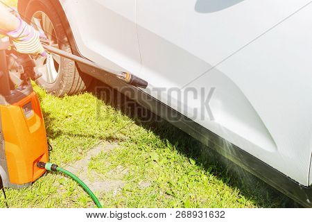 Manual Car Wash With Pressurized Water In Car Wash Outside. Summer Car Washing. Cleaning Car Using H