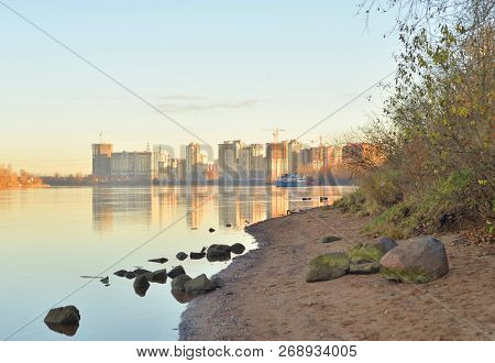 Coast of Neva River and modern residential buildings under construction on the outskirts of St. Petersburg at sunny autumn evening, Russia. poster