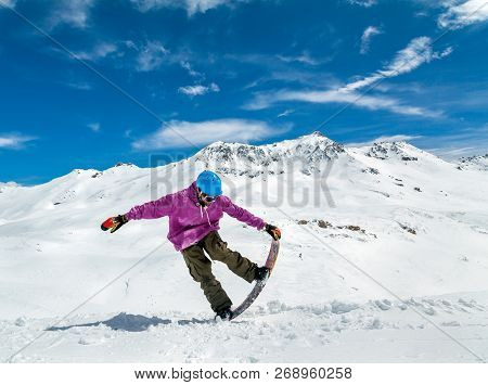 Snowboarder In Mountains Taking For The Edge Snowboard Against The Blue Sky And Clouds
