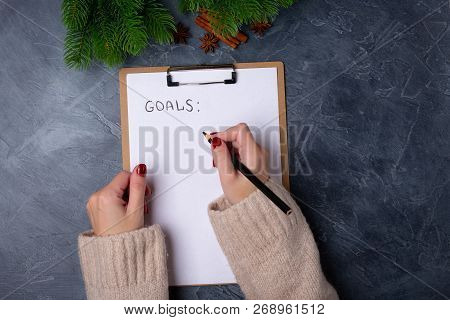 Woman Hands Ready To Write Goals On Blank List On Dark Background. Flat Lay. Top View. New Year Conc