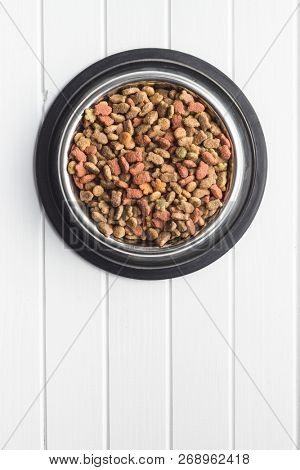 Dry pet food. Dry kibble food in metal bowl. poster